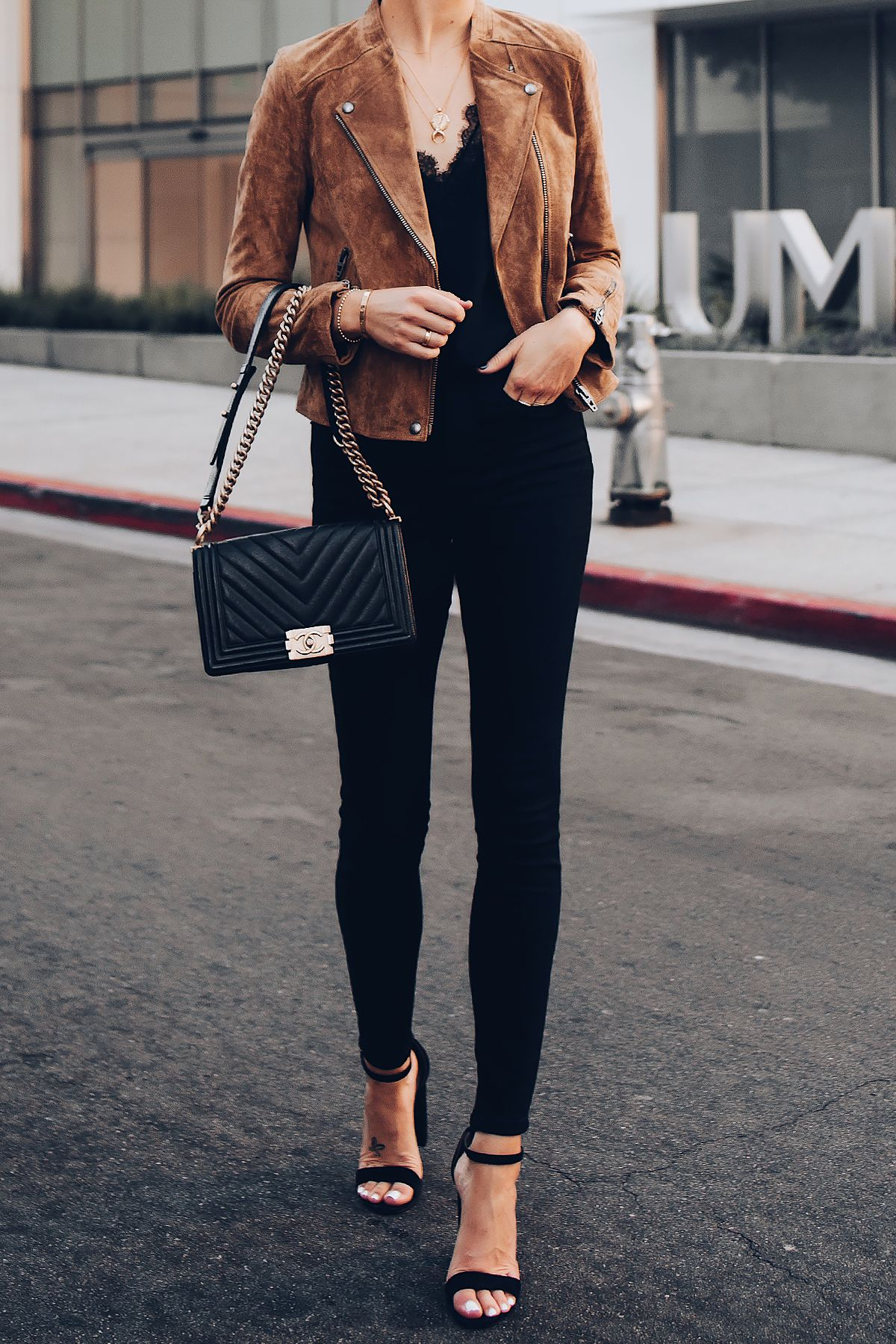 36d1e938dd7 Blonde Woman Wearing Blanknyc Tan Suede Moto Jacket Black Lace Cami  Everlane Black Skinny Jeans Black Ankle Strap Heeled Sandals Chanel Black  Boy Bag ...