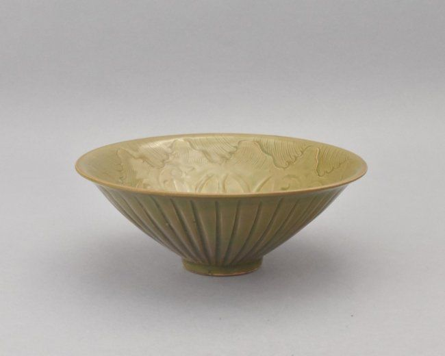 "VERY FINE YUE WARE CELADON BOWL, Having narrow central body with slightly flared rim. Three lotus blooms encircling the centralized chrysanthemum medallion, surrounded with tendrils of scrolling wavy water, all reserved in pale-celadon underglazed. 3"" H x 7-7/8"" Diam."