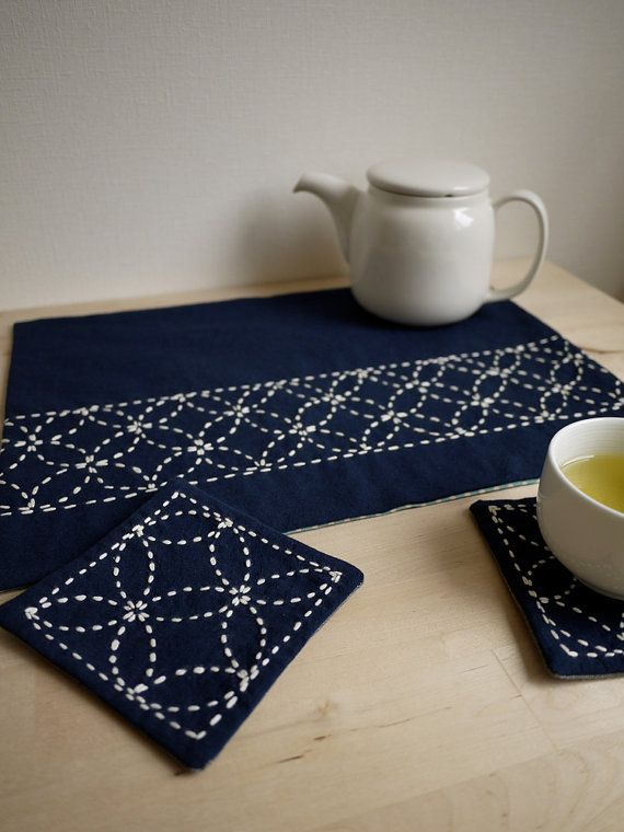 Unique sashiko designs you can make yourself! This craft kit provides all the materials youll need to create your own set of one placemat and 2 coordinating coasters. This kit includes: - - Original Saké Puppets pattern(s) - - Fully illustrated instructions - - Carbon paper for tracing pattern(s) onto fabric & tracing plastic - - Sashiko needle - - Sashiko yarn (100% cotton) - - Indigo blue fabric (100% cotton) - - Backing fabric in light gray cotton with white polka dots To comp...