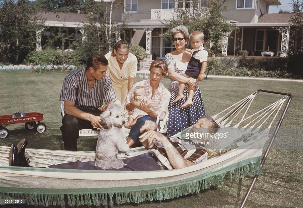Surrounded by his family, American movie producer, artist, and animator Walt Disney (1901 - 1966) lies in a hammock in the garden, with a poodle on his lap, 1950s. Among those pictured are his wife, Lillian (nee Bounds, 1899 - 1997) (left, in sunglasses), and their daughters Sharon (1936 - 1993) and Diane (1933 - 2013).