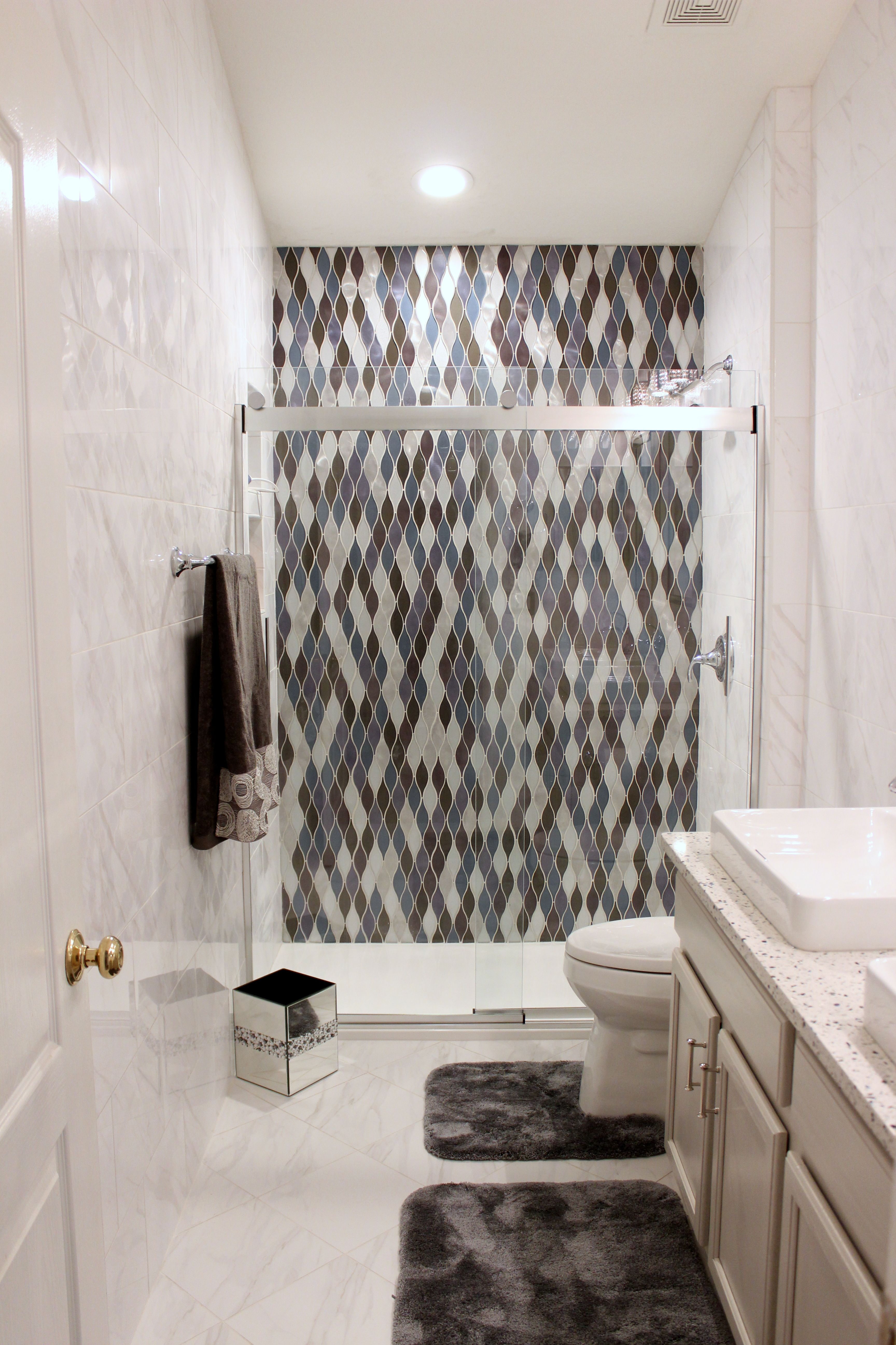 This Guest Bath Features A Stunning Shower Accent Wall Floor To Ceiling Tile Walls Recylced Glass Counter Bathroom Shower Half Wall Shower Bathroom Wall Tile