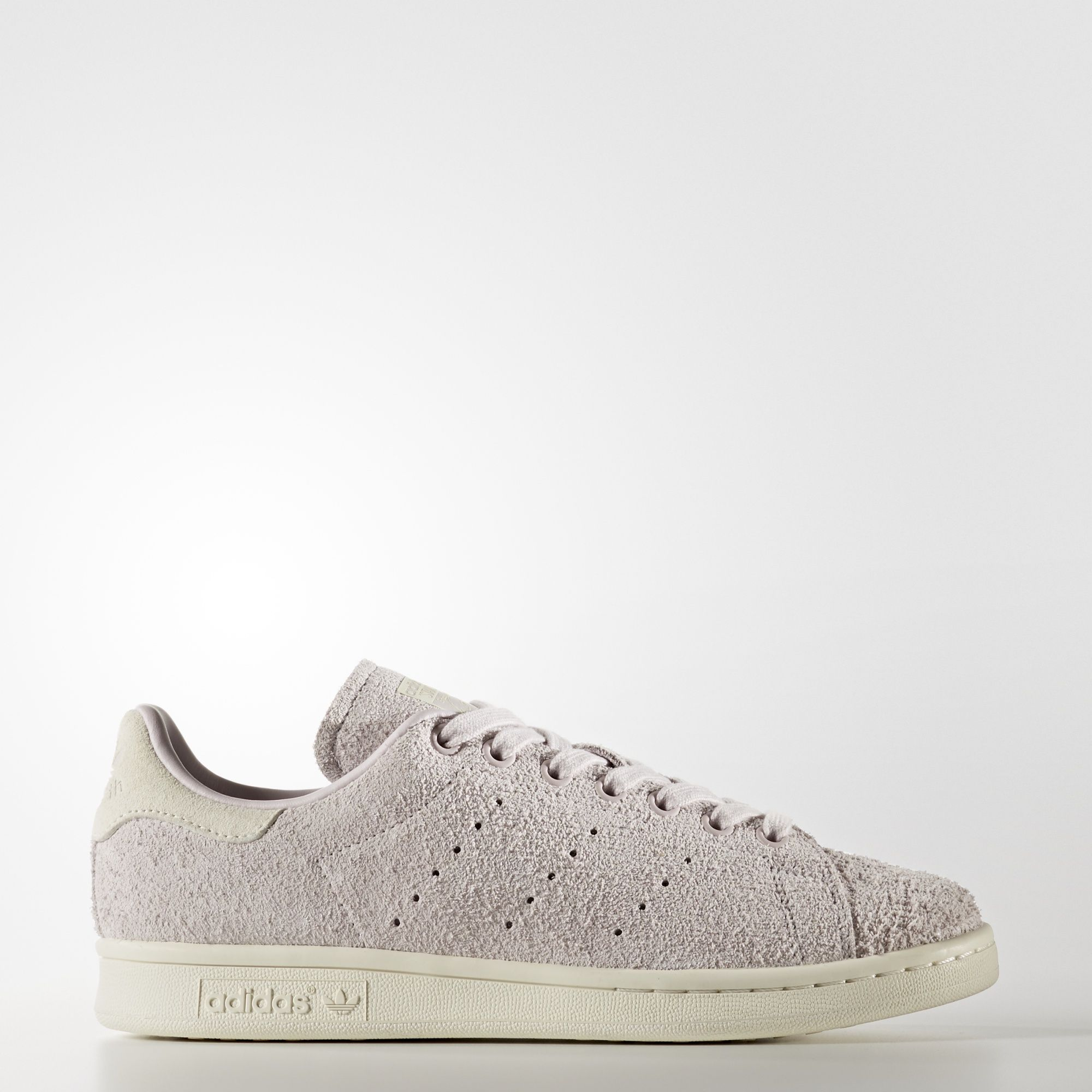 A true classic never goes out of style. These women's shoes have the clean look and signature lines of the original Stan Smith sneaker, remade with a textured suede upper. A contrast heel tab and perforated 3-Stripes preserve the heritage design.