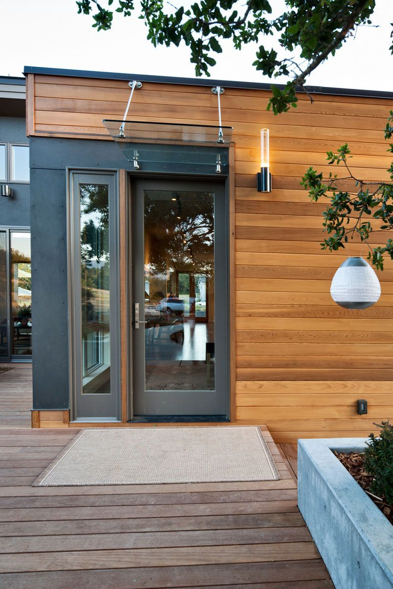 Pensive Prefab Home to be a Refreshing Place : Awesome Entrance Door With Transparent Glass Canopy And Torch Like Contemporary Wall Lamp Of Wooden Prefab Home