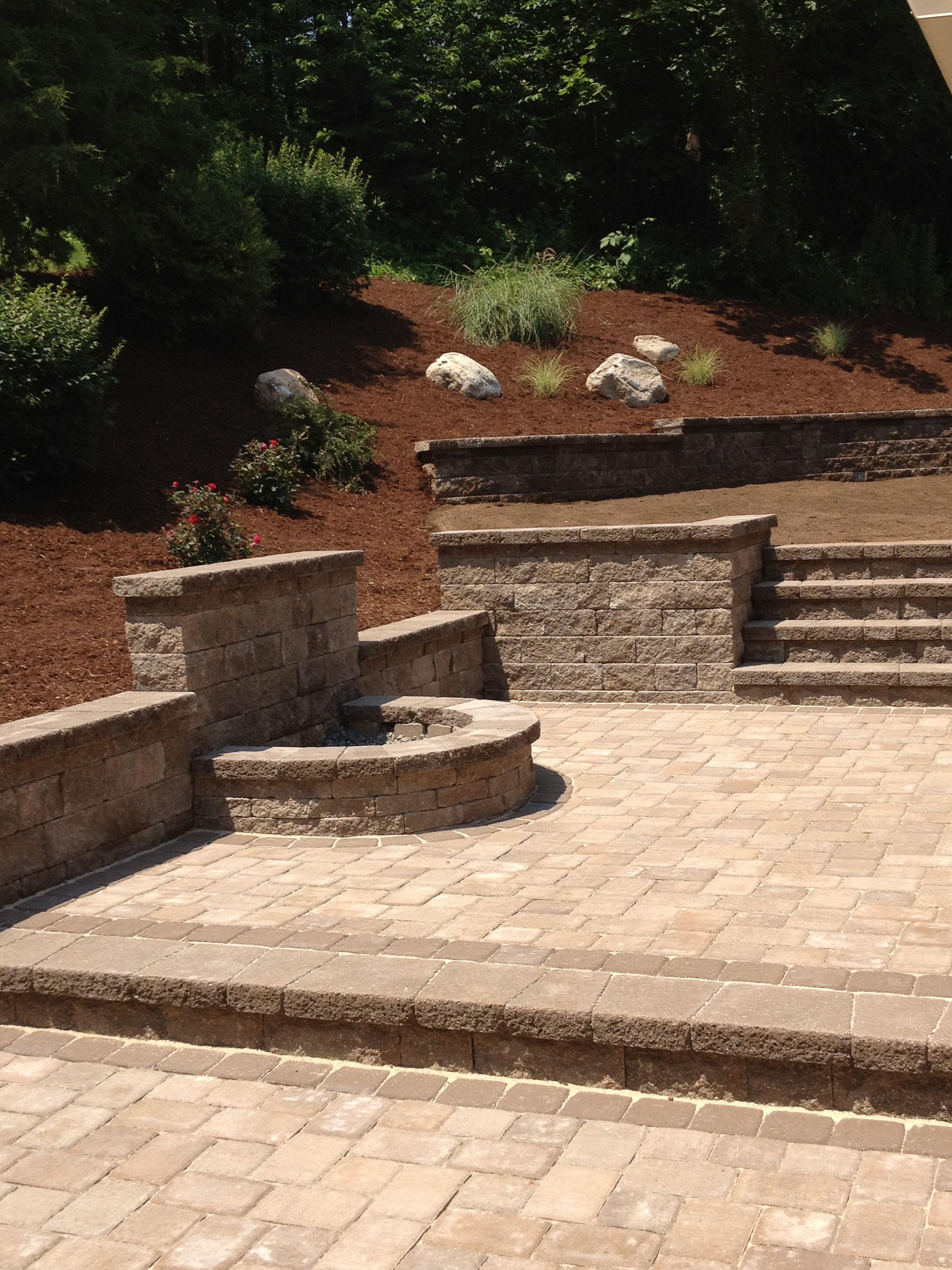 Fire pit borders a mini creta paver patio with retaining walls