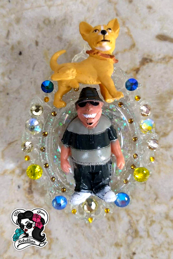 This hilariously fun brooch was created by Santa Fe artist Maria Delgado-Rooks. This brooch features a dog above his owner about to have a quick bathroom break. The Homie and dog are set into a beautifully crafted brooch that is clear with glitter. Blue, yellow and orange rhinestones are set in the brooch around the pair.  #ggr #homies #nostalgia #femaleartist #chicanaartist #hispanicculture #hispanicownedbusiness #hispanicart #hispanicartist #mexicanartist #mexicanculture #handcrafted