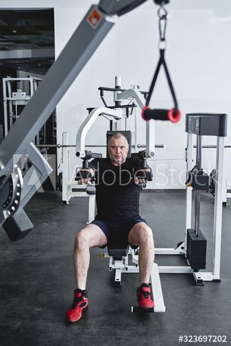 Adult gray-haired man trains on fitness equipment in the gym, pumps legs and arms muscles, loses wei...