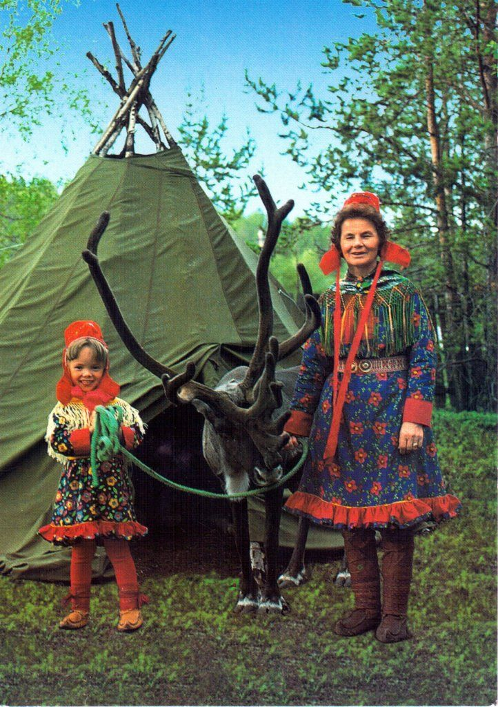 A Sami woman and child with their reindeer. Findland