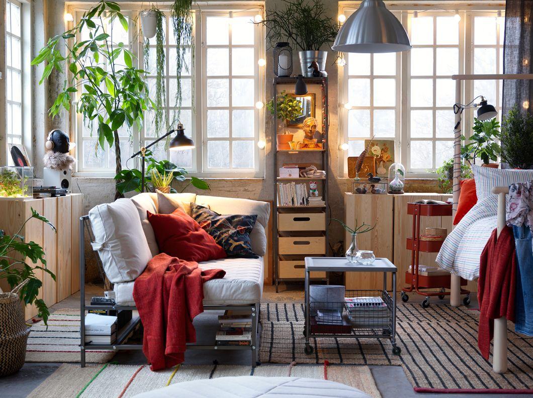 Afslappet stue med hvid sofa med bøger og andre ting på en indbygget ...