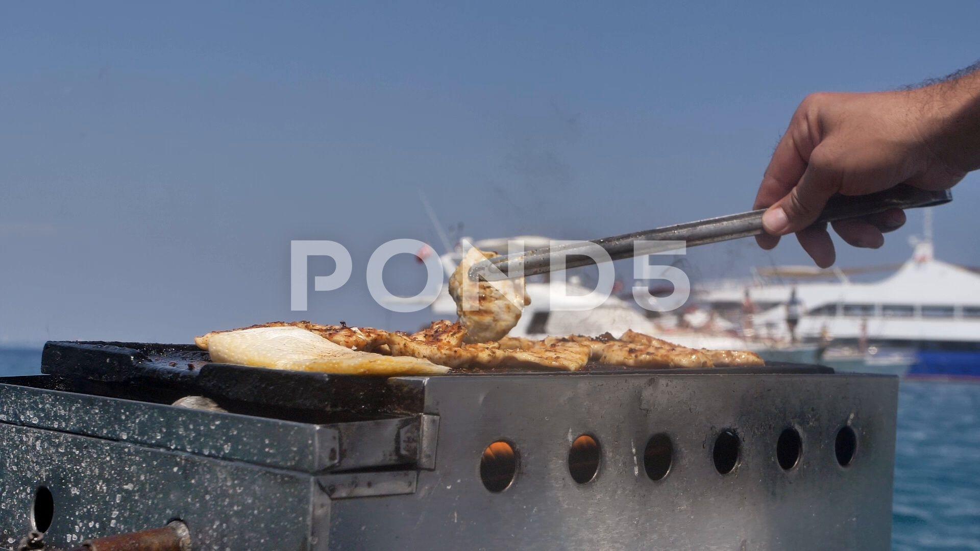 A man fries meat near the ocean twists it on the grill Fire burns in the iron Stock Footage oceantwistsmeatman