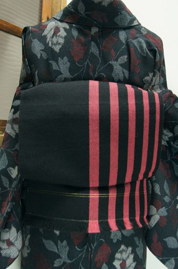 シックなブラックに優しく映えるコーラルピンクのストライプがモダンなウール名古屋帯です。
