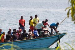 African people in boat lift the anchor. Royalty Free Stock Photo