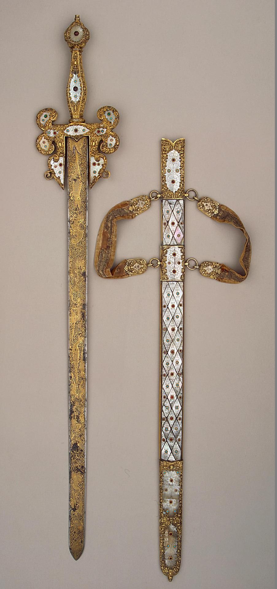 Sword Italy, Middle - second half of the 16th century Outwardly this sword - in particular the configuration of the hilt and scabbard, and of course the decoration of gilded silver, mother-of-pearl and coloured stones - would seem to have been intended for official or ceremonial use. The nature of the decoration on the blade and the technique of gold inlay on a blued ground, indicate that it may have been made in a Venetian