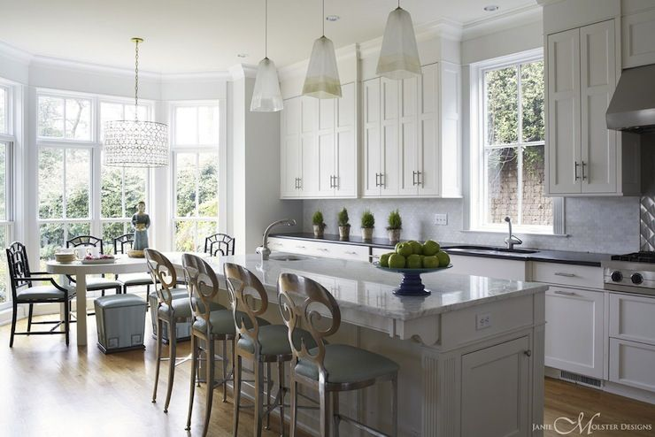 Four Silver Metal Barstools With Curvy Backs Line The Edge Of The Kitchen  Island. Three