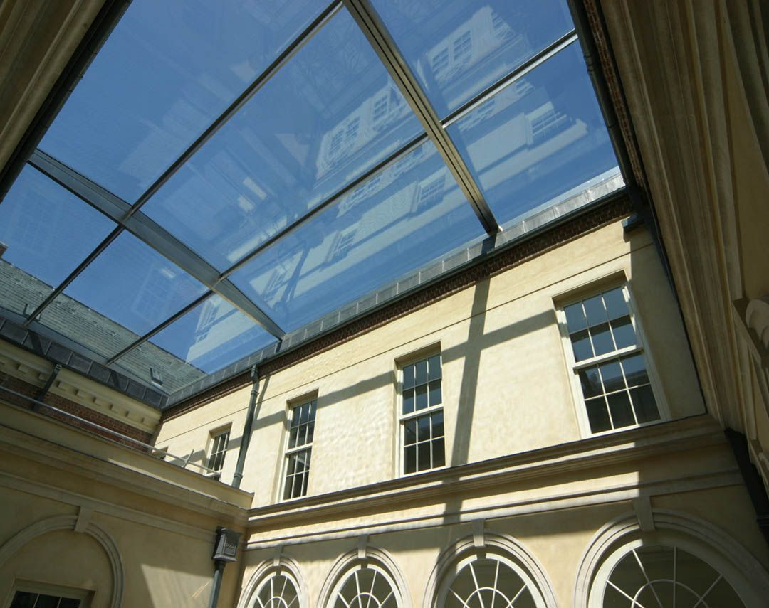 Large Retractable Roof Over Courtyard Of Listed Building. Vast Pieces Of  Glass Are Set Onto A Gently Arched Frame.