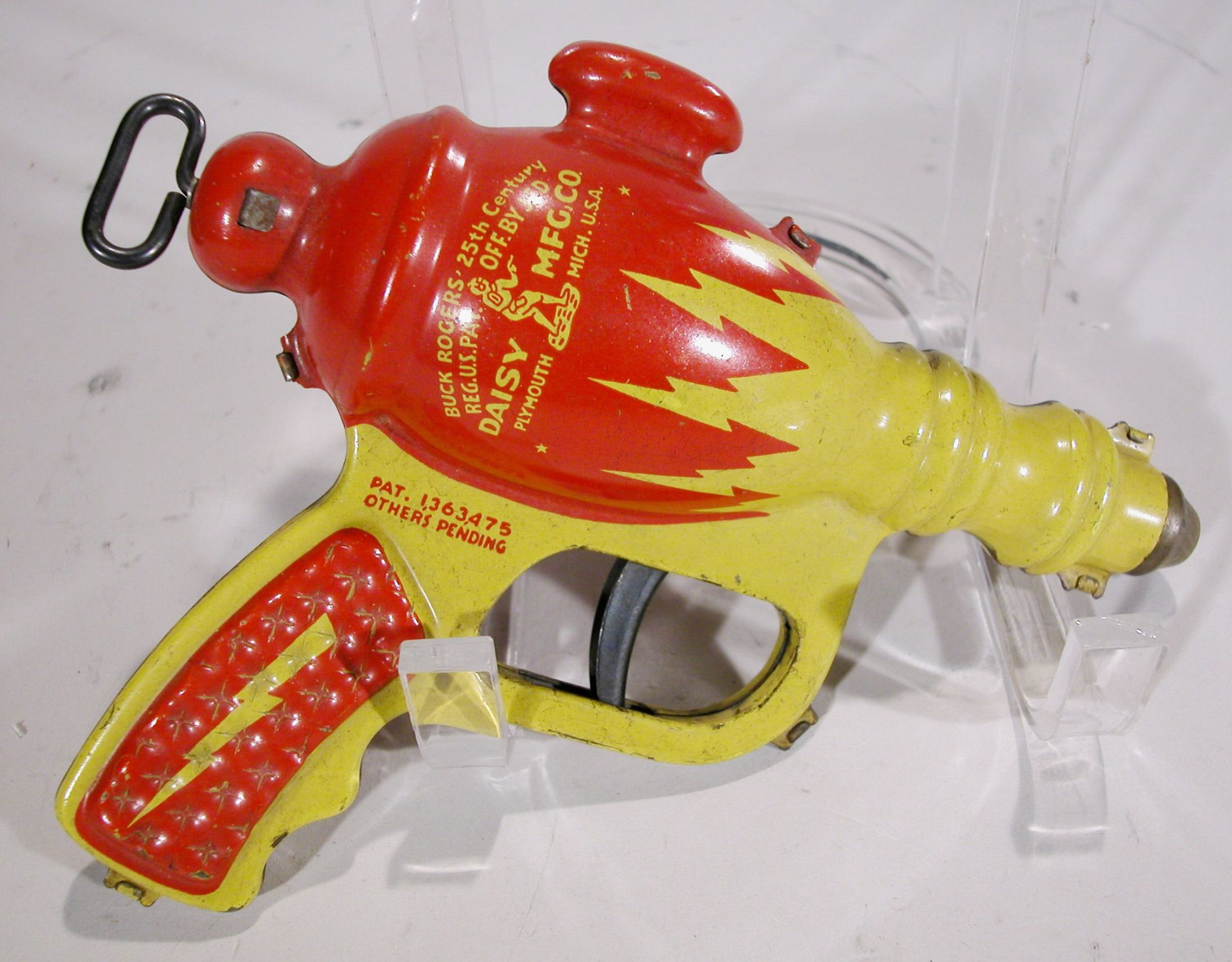 This is a Buck Rogers XZ-44 Liquid Helium Toy Water Pistol manufactured by Daisy Manufacturing Co. in 1936. Inside the toy's metal body, where the red and yellow lightning bolts meet, a leather sack held the water for this water gun. The gun was also issued in a solid copper-colored finish, which has become the more rare of the two versions.