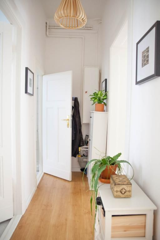 Heller Flur mit Holzboden, weißen Wänden und Türen sowie kleinem - flur idee