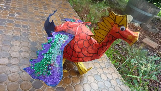 dragon pinata made using a balloon, toilet paper rolls, and tissue paper