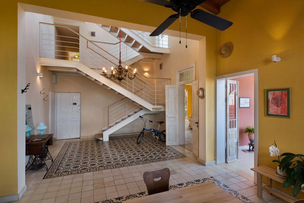 """קומת הכניסה היא החלק המרכזי בדירה. גודלה 120 מ""""ר, והיא מתנשאת לגובה של שלושה מפלסים: התקרה המשופעת מיתמרת בשיא גובהה לשבעה מטרים ו-30 ס""""מ, ובאזור הנמוך היא מגיעה לשישה מטרים """"בלבד"""". הדלת הראשונה מימין מובילה למרפסת, וזו שקרובה למדרגות מובילה לסלון (על אף שהשלט שתלוי לצד הדלת מודיע שיש שם מועדון קצינים) ( צילום: אסף פינצ'וק )"""