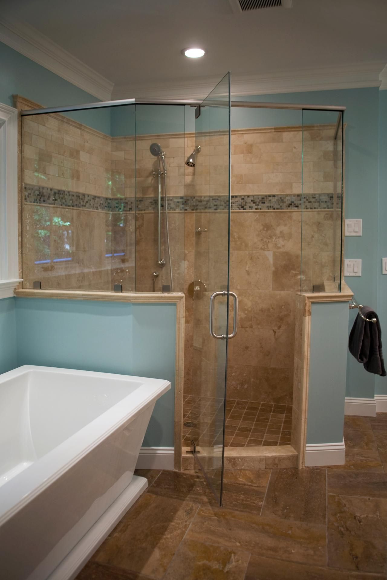 This light blue master bathroom features a spacious glass enclosed ...