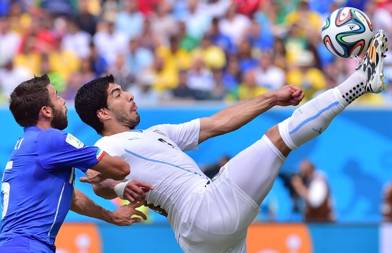 El delantero uruguayo Luis Suarez control la pelota frente a Andrea Barzagli de Italia. (AFP PHOTO  GIUSEPPE CACACE)