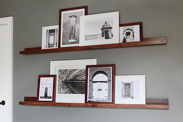 Photo Frames On Top Of Dark Stained Wooden Shelves Attached To A