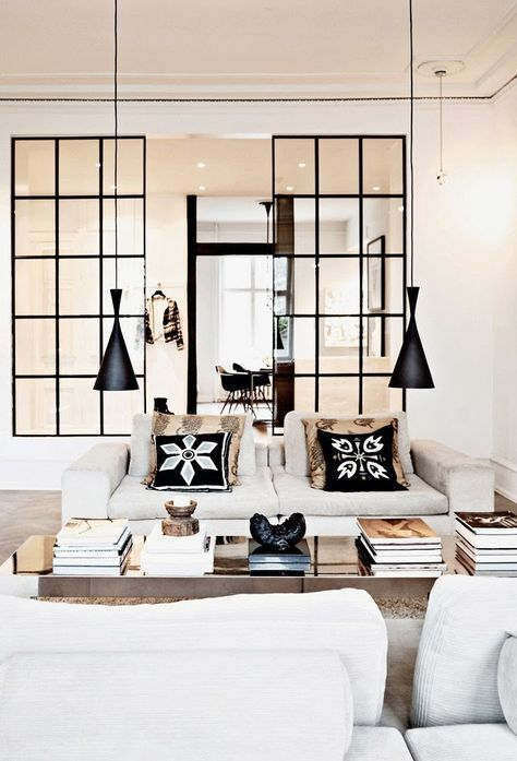 Very Elegant Living Room With Two Black Lamps And Lots Of Coffee Table Books