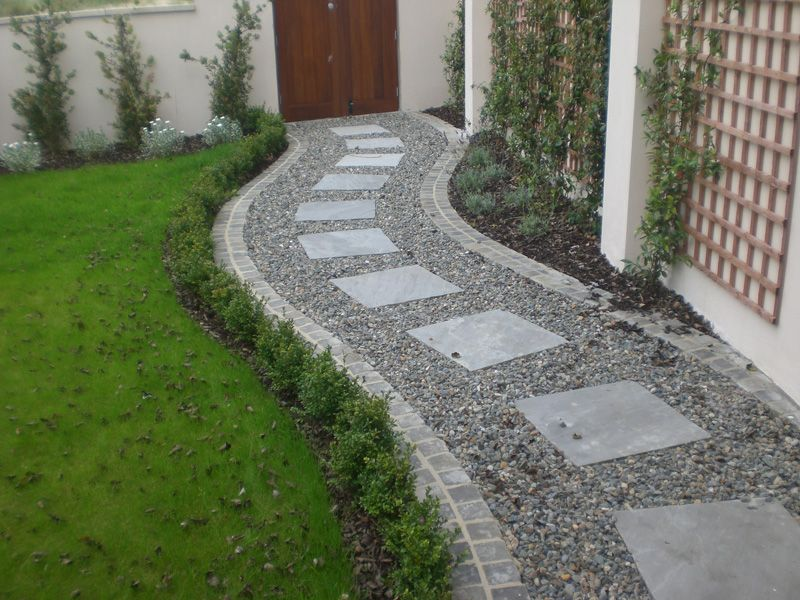 Square paving stones in a curving gravel path by a lawn for Paving garden designs