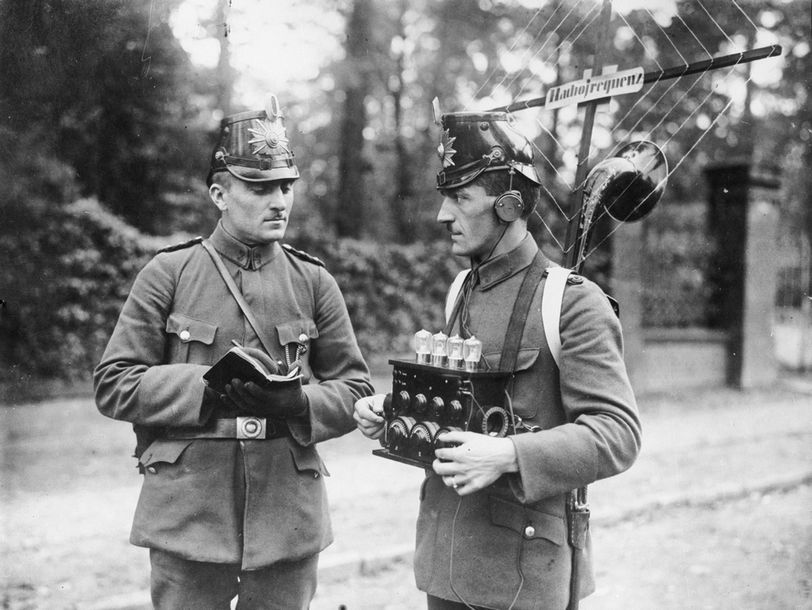 A member of the German wireless police picks up signals on the radio equipment he carries on his back, while his colleague takes notes. (Pho...