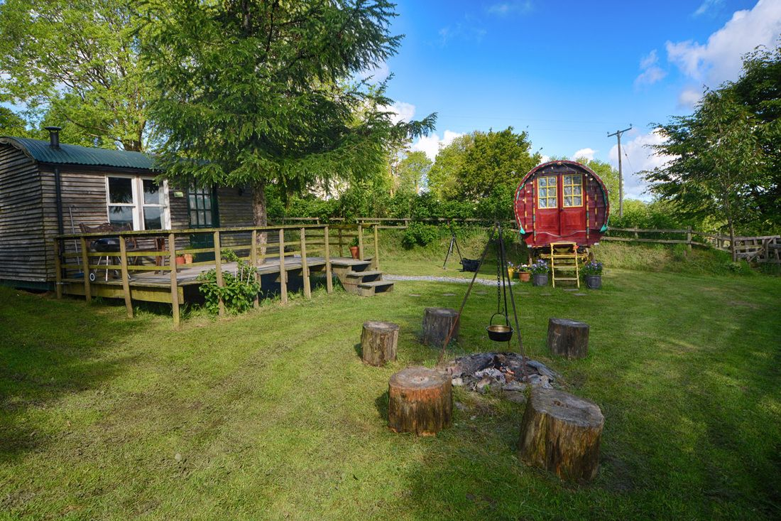Old Oak Gypsy Wagon, Carmarthenshire. Alongside the wagon is the log cabin, which has a private decked area with a handmade bench and table and in front an open fire pit for your use http://www.organicholidays.com/at/3177.htm