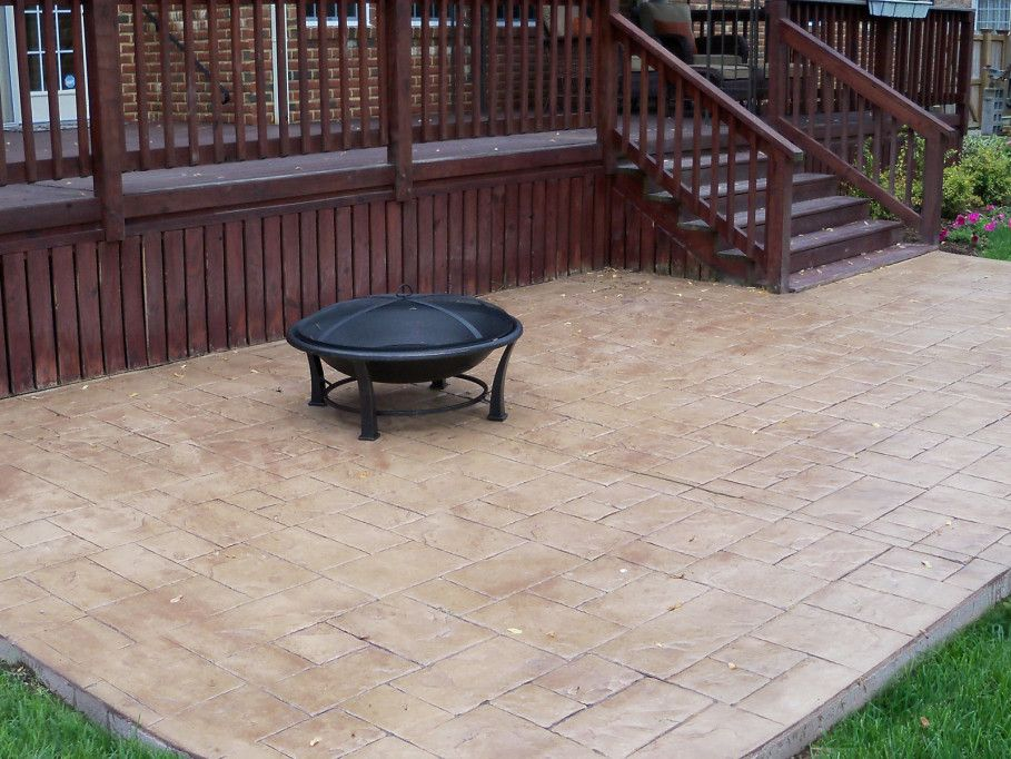 Simple Brown Stamped Concrete Patio And Black Round Fire