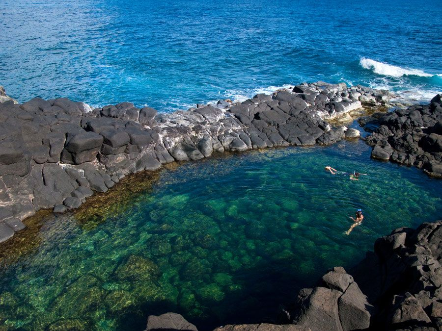 Two small waterfalls flow into Queen's Bath, a scenic, bathtub-shaped tide pool located on the north shore of the Hawaiian island of Kauai.