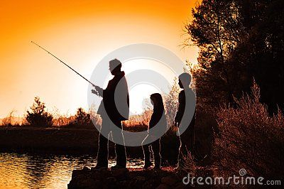 A family outing outdoors.  children looking on while father is fishing