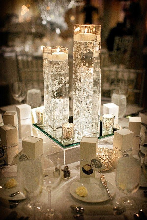 centro de mesa con base de vidrio y jarrones con velas