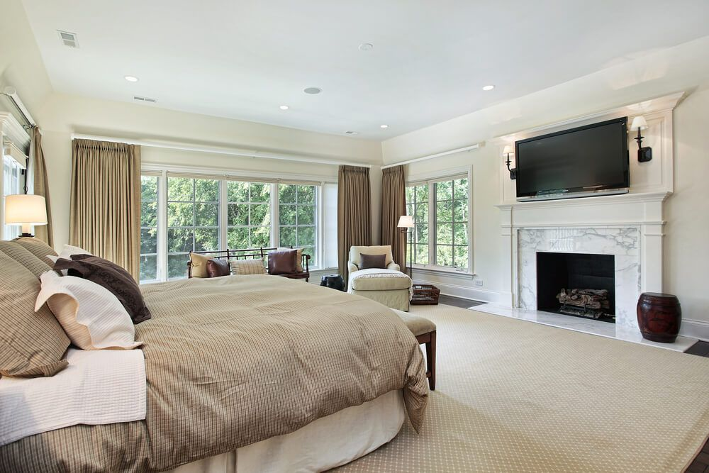 Large corner bedroom with white marble hearth and TV mounted above  beige  carpeting matching the bed set and curtains. How To Decorate A Large Bedroom  Decorate Large Bedroom Corner