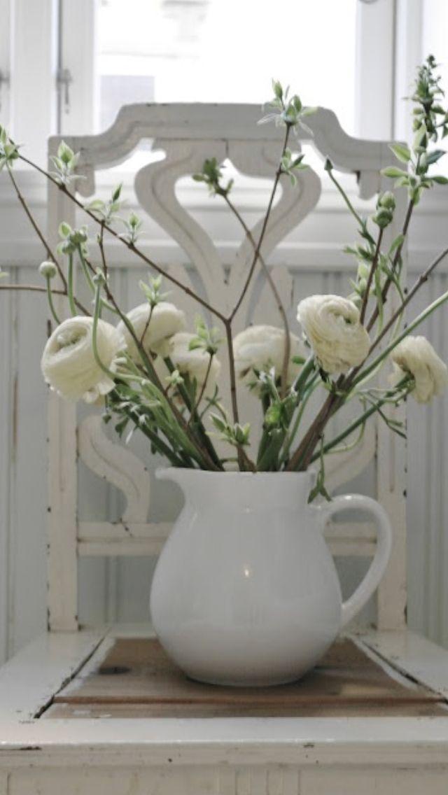 Rustieke vaas met ranonkeltjes en bloesem