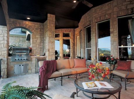 An outdoor kitchen defined by an arched stone wall adjoins ... on Outdoor Living Space Builders Near Me  id=91085