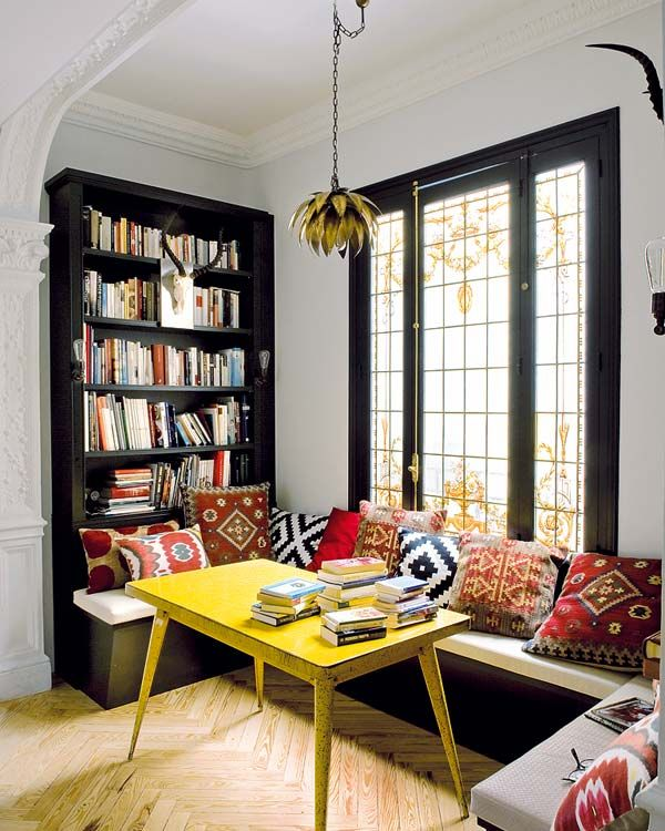 Eating/ reading nook with ethnic pillows, yellow table and built in book storage. Black trimmed windows.
