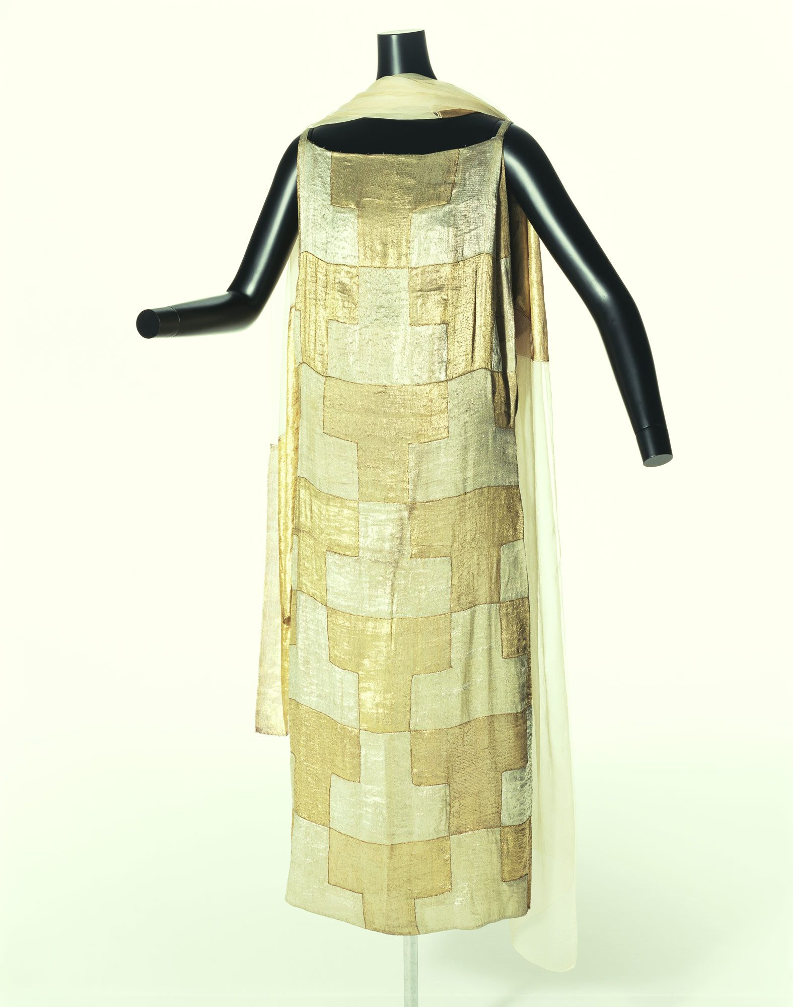 """Henriette"" Evening, Madeleine Vionnet: ca. 1923, lamé plain weave pieced into two checkerboard pattern, plain weave and crêpe stole. ""...The front and back panels are patchworks, constructed from 28 silver and 28 golden patches in a checkered pattern, and their similar design and texture are reminiscent of Japanese lacquer-ware such as ""Makie."" Madeleine Vionnet was interested in Japanese kimono and fine arts, and in the early 1920s she created many works that seemed to be inspired by…"