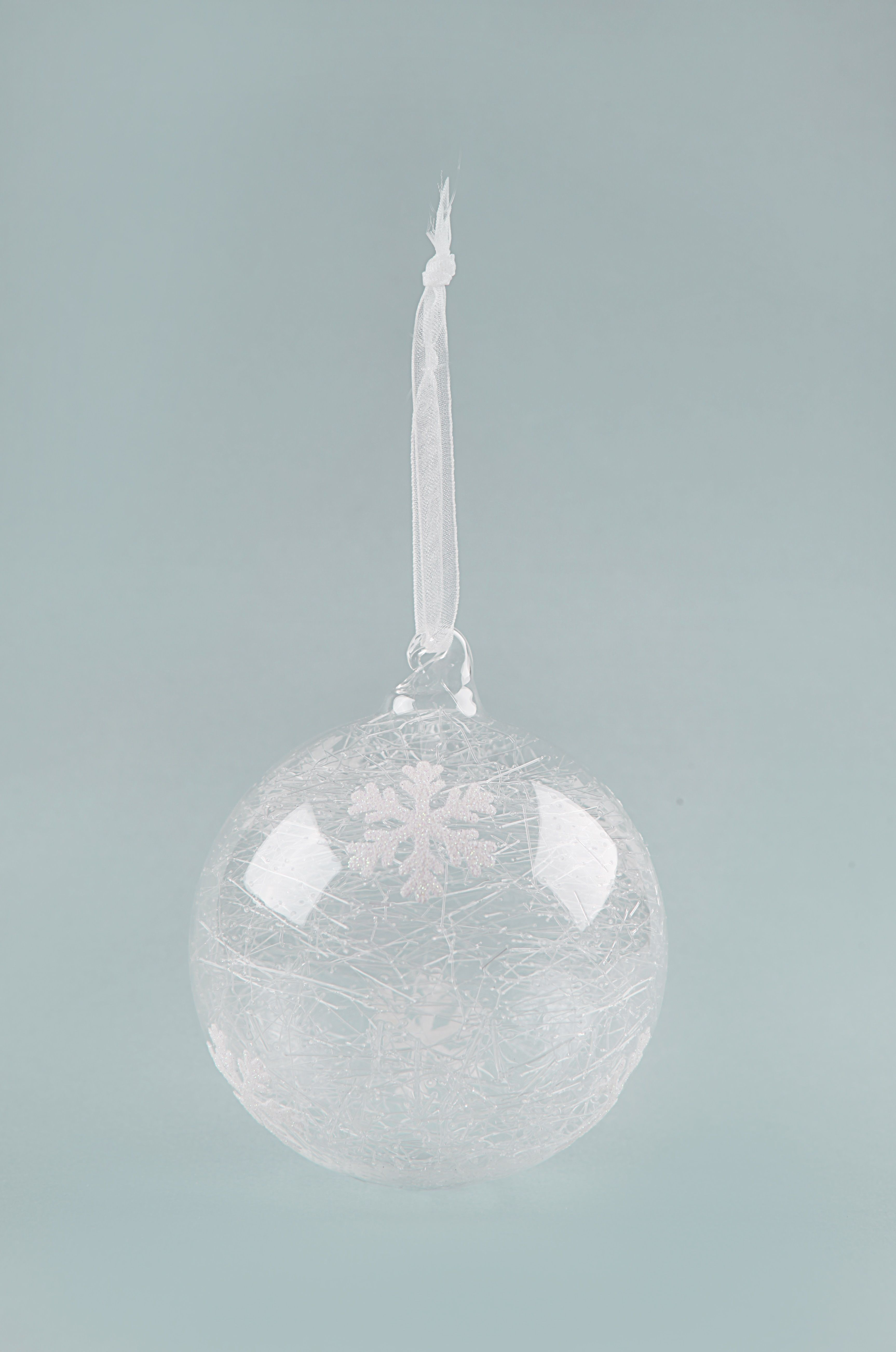 This Glass Snowflake Bauble is an unusual piece. Within the bauble there is a snowflake and glass fibre which gives like a blizzard effect.