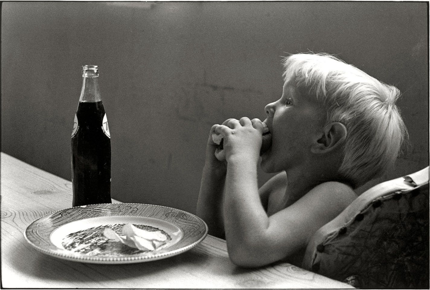 "Little boy taking a bite of food at the table."" Leatherwood, Kentucky, 1972. ""Cornett family. Print from a 35mm negative by William Gedney. Gedney Photographs and Writings Collection, Duke University."