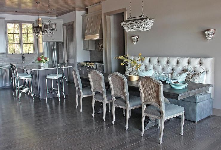 Contemporary dining room features a Pottery Barn Clarissa Glass Drop Rectangular Chandelier illuminating a two tone tufted dining banquette facing a trestle dining table lined with French cane back dining chairs.