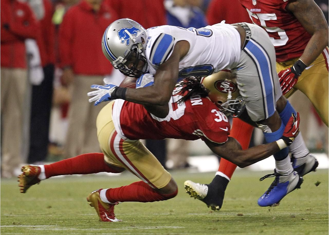 Detroit Lions running back Kevin Smith, top, is upended by San Francisco 49ers free safety Dashon Goldson
