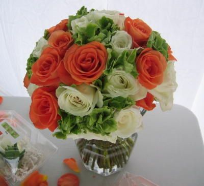 Orange and creamy white roses are swirled with green hydrangea
