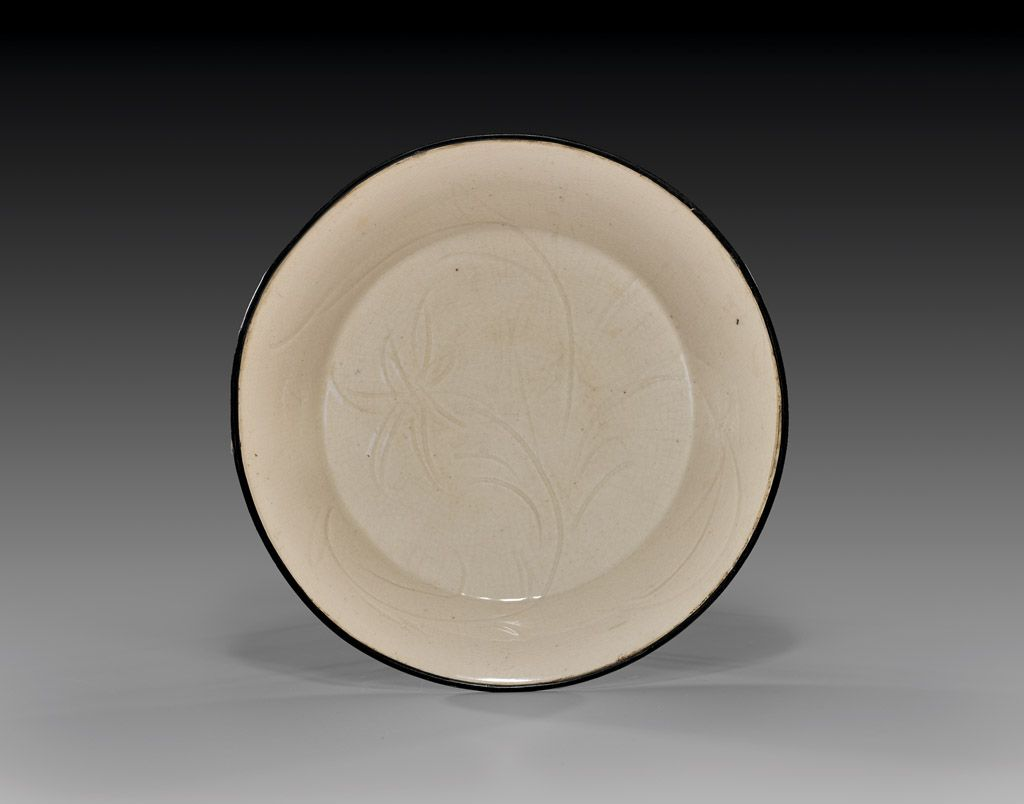 """SONG DYNASTY DINGYAO GLAZED DISH   宋 定窯白釉劃花盤  Fine Chinese Song Dynasty Dingyao glazed dish; the circular footed form incised with a single blossom and foliage, and mounted with copper rim; D: 6 1/2""""; Provenance: Wimmer Collection, La Jolla California   Estimate $2,500-3,500"""