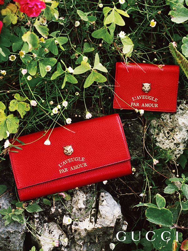 """36dfb375d96 Presenting gifts from the Gucci Garden. Red leather wallets featuring a  feline head and the phrase """"L Aveugle Par Amour"""" by Alessandro Michele."""