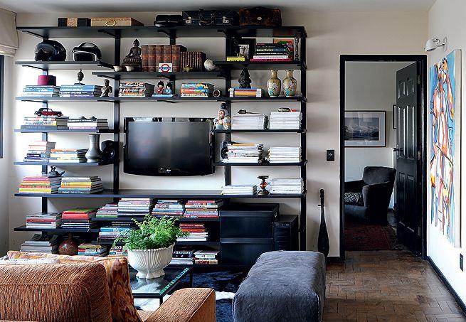 A estante do living do designer Augusto Perez, junto à porta do quarto, tem estrutura de barras de ferro chatas com prateleiras de MDF texturizado de preto