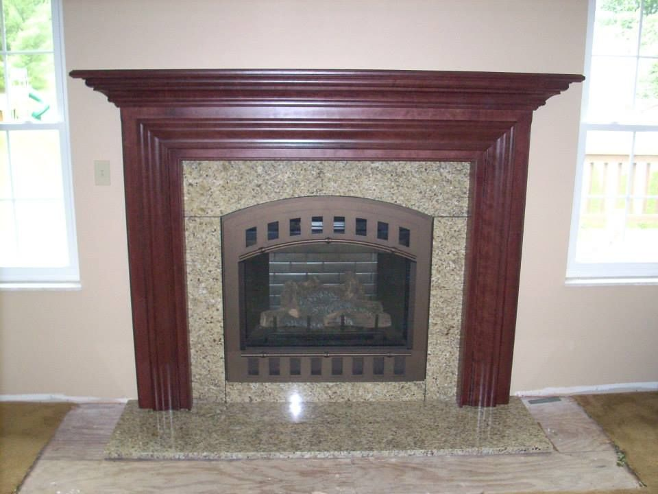 A Dark stained Delaware mantel with the beautiful @Heatilator Fireplaces Fireplaces Caliber fireplace and arched Contour front granite surround