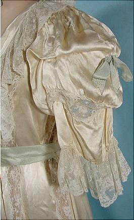 c. 1900 Ecru Silk Satin Fancy Dressing Gown. Ecru, extra fancy design, wrap front, puff sleeves dripping in lace. Original very light blue silk ribbon at neck to tie at waist, and bows on sleeves. Tiny decorative tucks at the waist in front. Detail