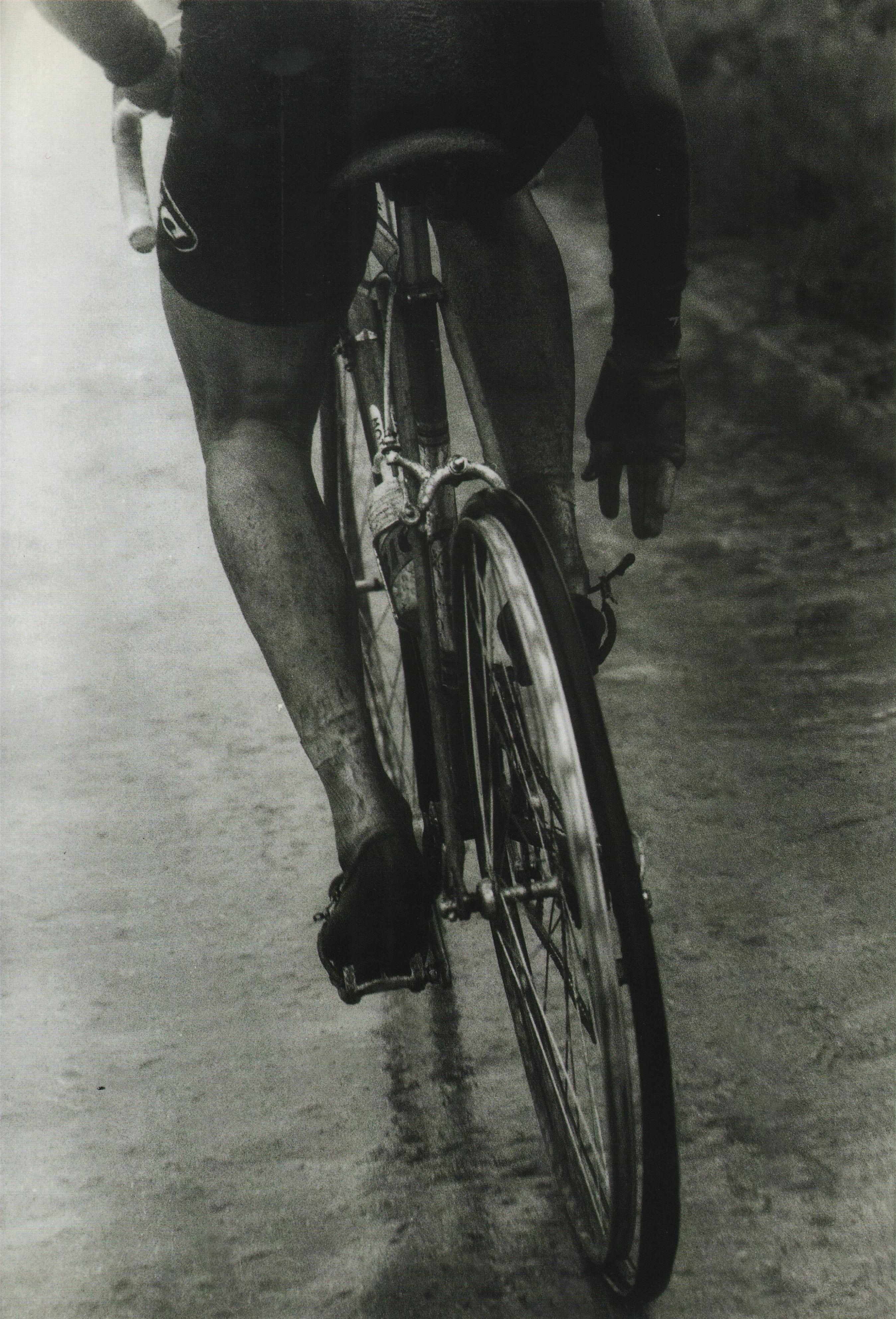 Giro d'Italia 1967. 19^Tappa, 8 giugno. Udine > Tre Cime di Lavaredo. Il Giro è quel del cinquantenario, il tempo da lupi. Il fotogramma coglie l'attimo in cui la ruota posteriore di un ciclista della squadra BIC, forse Lucien Aimar, si sta smontando, con lo pneumatico che si sfila dal cerchione: la reazione del corridore è pronta e subito allenta il fermapiede, l'incidente ancora una volta è solo sfiorato...