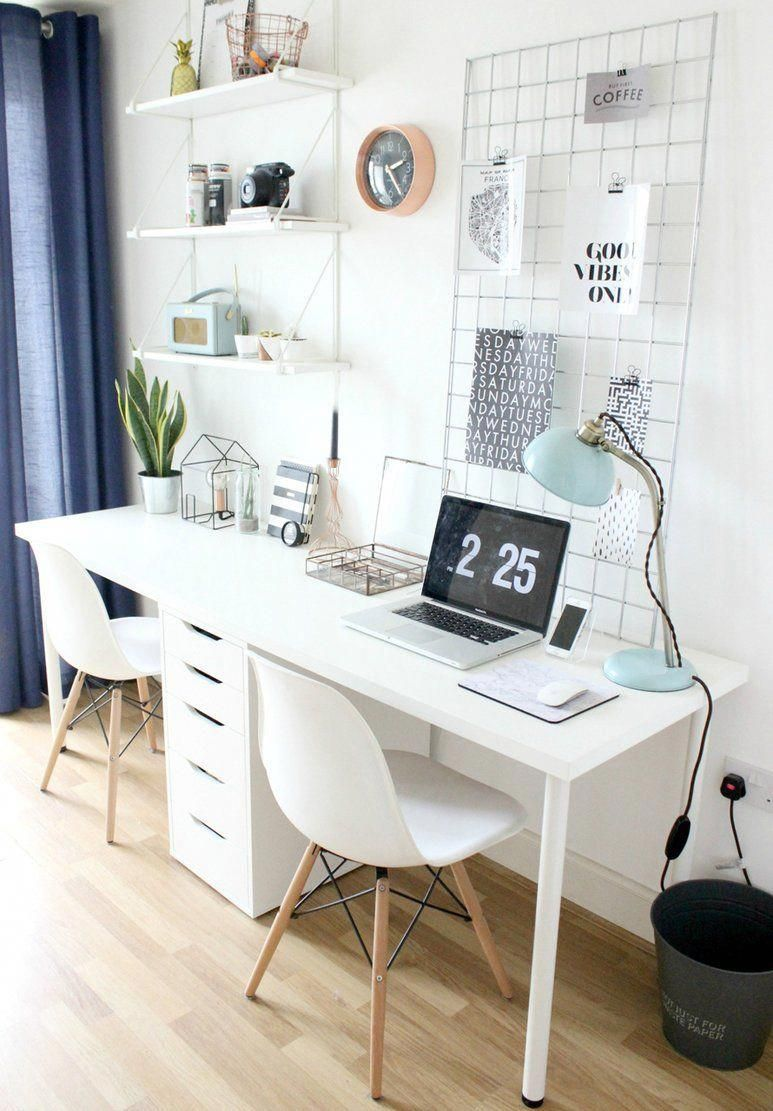 A minimal scandistyle home office with a white desk and two chairs